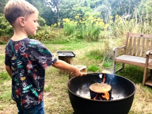 Boy toasting marshmallows over fire